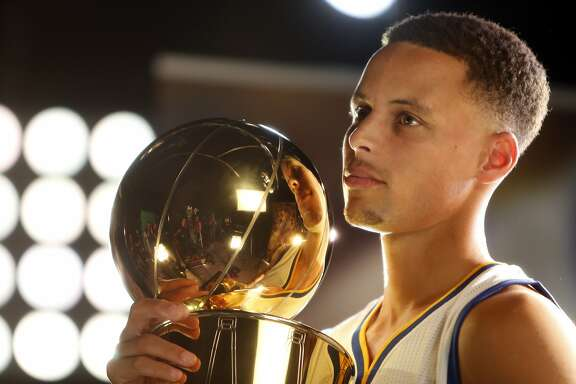 Stephen Curry does  a video shoot with the Larry O'Brien Memorial Trophy during Golden State Warriors' Media Day in Oakland, Calif., on Monday, September 28, 2015.