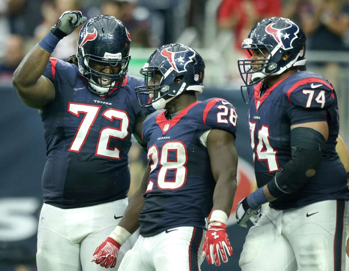 Houston Texans running back Alfred Blue (28) celebrates his 20-yard touchdown run against the Tampa Bay Buccaneers with tackle Derek Newton (72) and tackle Chris Clark (74) during the fourth quarter of an NFL football game at NRG Stadium on Sept. 27, 2015, in Houston.