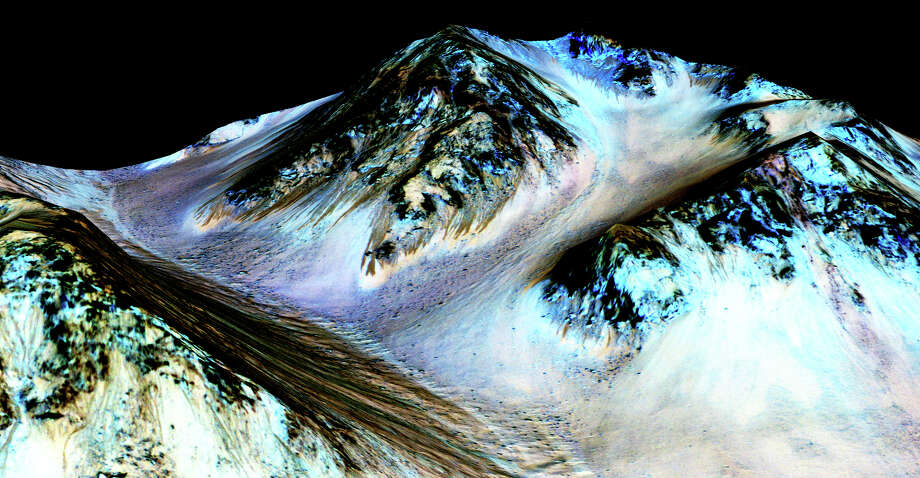 Scientists say observations from NASA's Mars Reconnaissance Orbiter of dark, narrow streaks on the slopes of Mars' Hale Crater have detected salt crystals that contained water molecules. Photo: NASA /Getty Images / 2015 NASA