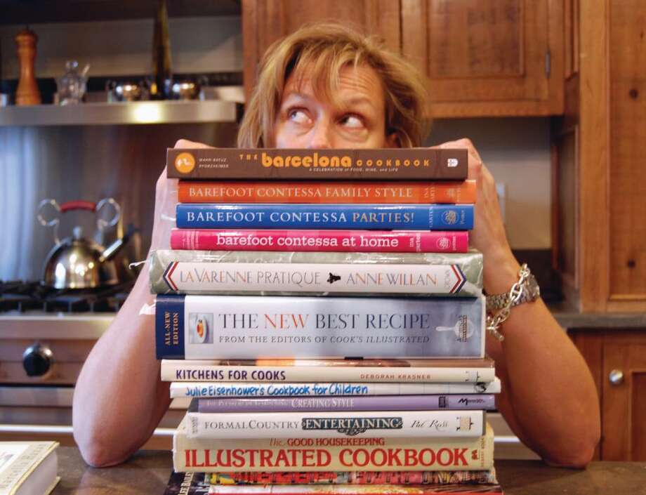 New Canaanite Pam Goodwin stands chin-high with cookbooks in her kitchen. Goodwin regularly plays host to friends and neighbors at dinner parties in her home. Photo: Jeanna Petersen Shepard / New Canaan News