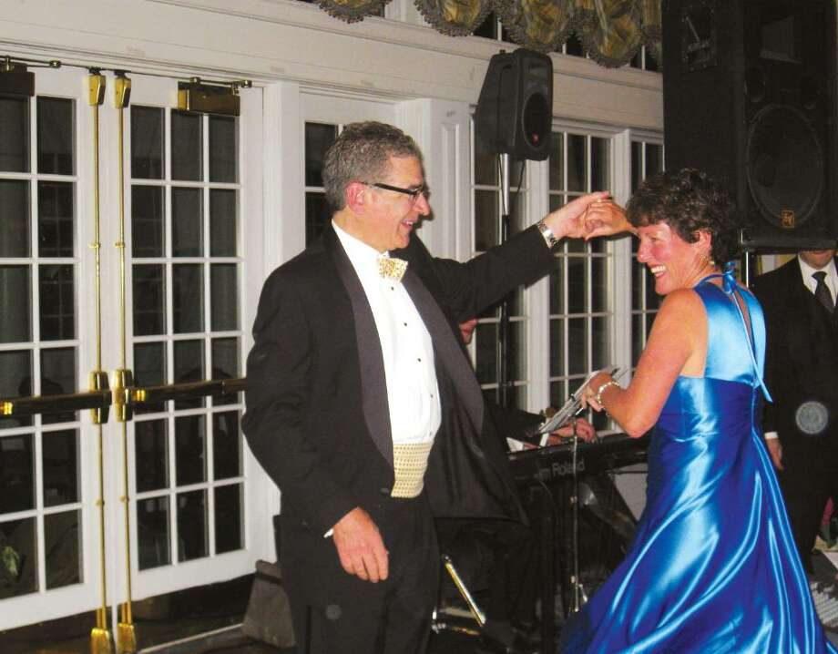 "Mike Franco passes his wife, Mary, under his arm during coctail hour at the Country Club of Darien during the New Canaan Dance Club's spring dance. The Franco's said they had no ballroom dance experience when they joined the social dance club in the mid-90's. ""For Mike and I, this is our favorite thing to do,"" Mary said. ""We've only ever missed two [events] in all the years we've been members—and we get mad when we do."" Photo: Brittany Lyte / New Canaan News"
