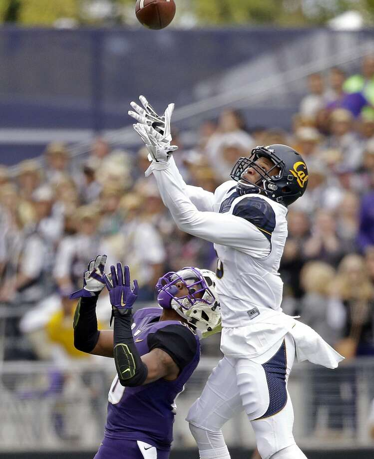 Cal's Darius White leaps above Washington's Marvin Hall to intercept a pass during the first half last Saturday in Seattle. Photo: Elaine Thompson, Associated Press