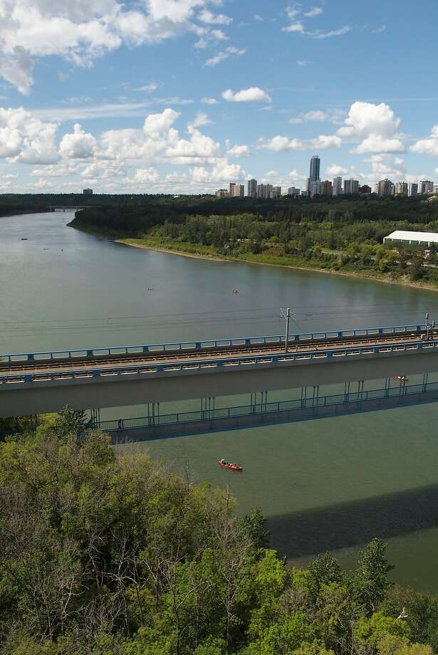 Kayakers paddle under a light-rail and pedestrian bridge that stretches over the North Saskatchewan River in Edmonton. The River Valley on either side is mostly protected green space and parks, including hiking and biking paths. Photo: Spud Hilton