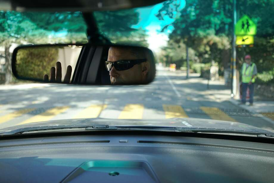 Los Altos Police Officer Steven Spillman waves at a crossing guard in Los Altos, Calif. on Monday, Sept. 28, 2015. Los Altos is statistically the safest city in the Bay Area which has seen a crime drop of 70% between 2013 and 2014. Photo: James Tensuan, Special To The Chronicle