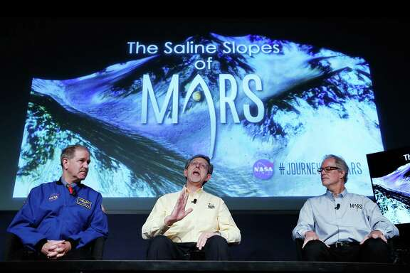 Mars appears to have flowing streams of salty water, at least in the summer, explained NASA scientists, from left, John Grunsfeld, Jim Green and Michael Meyer at a news conference.