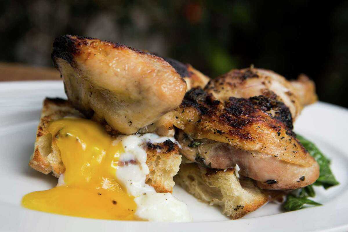 """Hunky Dory's Chicken and Eggs: Herb-rubbed half chicken with """"ember eggs"""" and greens on a baguette """"trencher."""" Monday, Sept. 28, 2015, in Houston."""