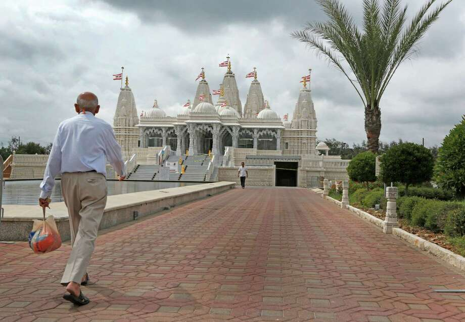 Devotees walk toward the BAPS Shri Swaminarayan Mandir Monday, Sept. 28, 2015, in Stafford. 