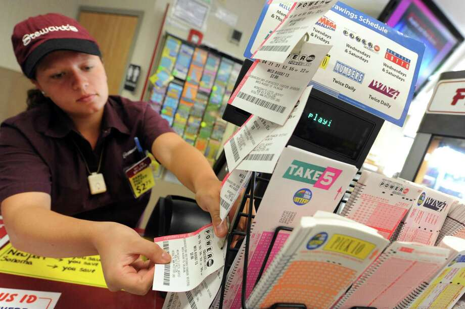 Sales associate Brianna Turner hangs Powerball quick picks from a clip tree at the Stewart's at Osborne and Sand Creek roads on Wednesday Aug. 7, 2013 in Colonie, N.Y. (Michael P. Farrell/Times Union archive) Photo: Michael P. Farrell / 00023458A