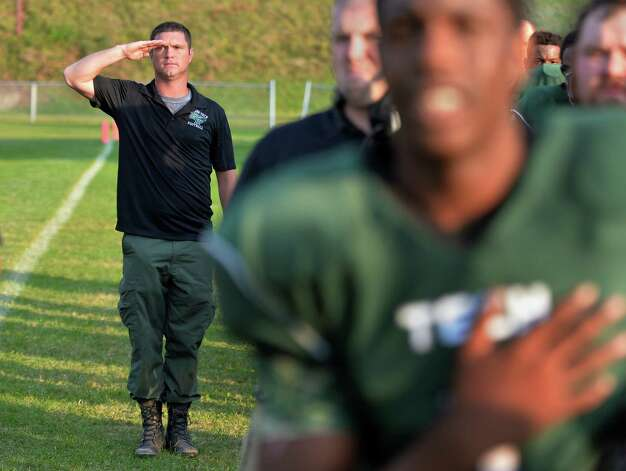 Green Tech head coach Travis Wood, left, a US Army veteran, snaps a salute as the National Anthem is player before Saturday's game against Scotia at Bleecker Stadium Sept. 19, 2015 in Albany, NY.  (John Carl D'Annibale / Times Union) Photo: John Carl D'Annibale / 00033441A