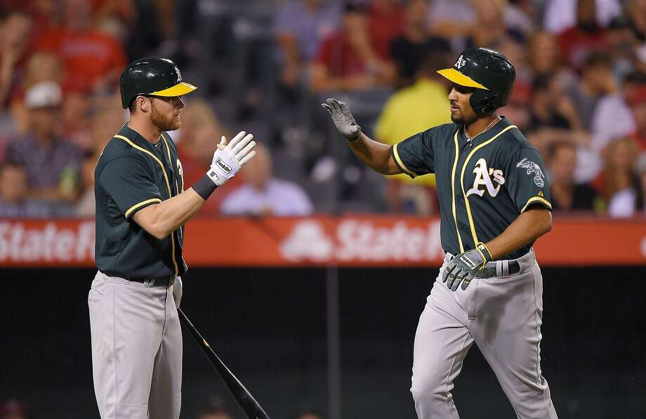 Oakland Athletics' Marcus Semien, right, is congratulated by Craig Gentry after hitting a solo home run during the fourth inning of a baseball game against the Los Angeles Angels, Monday, Sept. 28, 2015, in Anaheim, Calif. (AP Photo/Mark J. Terrill) Photo: Mark J. Terrill, Associated Press