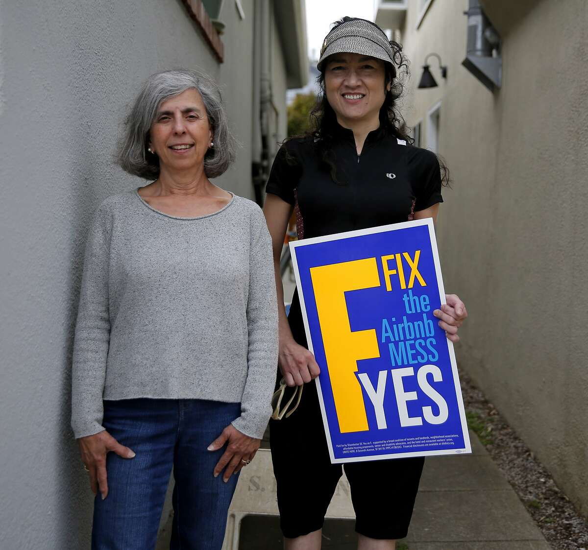Libby Noronha (left) and Mary Elder stand on the pathway between Noronha's house and her neighbor's house in San Francisco, California, on Monday, Sept. 28, 2015.