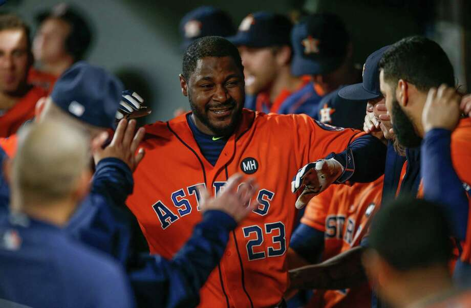 For the third consecutive game, Chris Carter receives a warm greeting in the dugout after homering, this time in the seventh inning Monday night at Seattle. Photo: Otto Greule Jr, Stringer / 2015 Getty Images