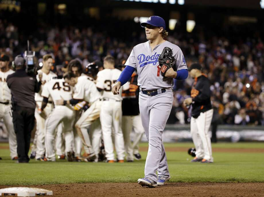 Los Angeles Dodgers' Enrique Hernandez walks off the field as the San Francisco Giants' celebrate a walk-off 3-2 win on a sacrifice fly ball from Alejandro De Aza in the 12th inning of a baseball game Monday, Sept. 28, 2015, in San Francisco. Photo: Marcio Jose Sanchez, Associated Press