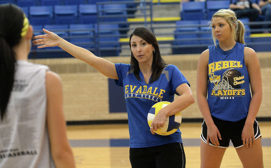 Evadale head coach Debbie Hollyfield recorded her 300th career victory last week when the Lady Rebels defeated Hull-Daisetta in four sets.  Evadale volleyball coach Debbie Hollyfield gives her players instructions on positioning during an after-school practice Monday. The Rebels are looking strong as they head into districts, and have their eyes set on advancing to the state play-offs.  Photo taken Monday, October 6, 2014  Kim Brent/@kimbpix     Manditory Credit, No Sales, Mags Out, TV Out, Web: AP Members only Photo: KIM BRENT / Beaumont Enterprise