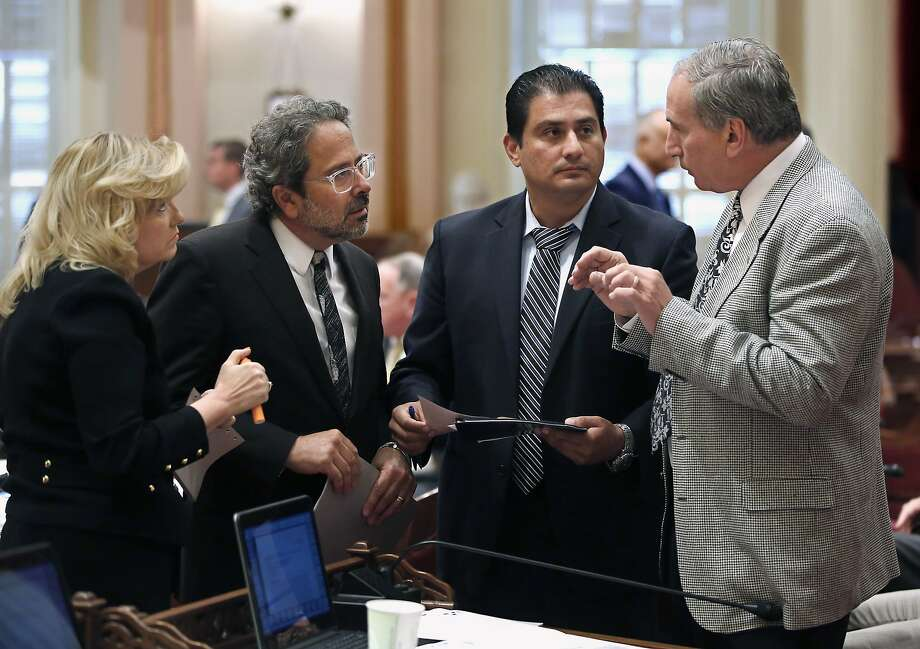 Democratic lawmakers Sen. Cathleen Galgiani of Stockton (left), Assemblyman Richard Bloom of Santa Monica and Sen. Ben Hueso of San Diego discuss amendment to Bloom's measure to phase out the use of microscopic beads in personal care products in California, to Sen. Jeff Stone, R-Temecula (Riverside County), in Sacramento. The state Senate approved Bloom's bill, after amendments were made that prompted many manufacturers and other business critics to drop their opposition. Photo: Rich Pedroncelli, Associated Press