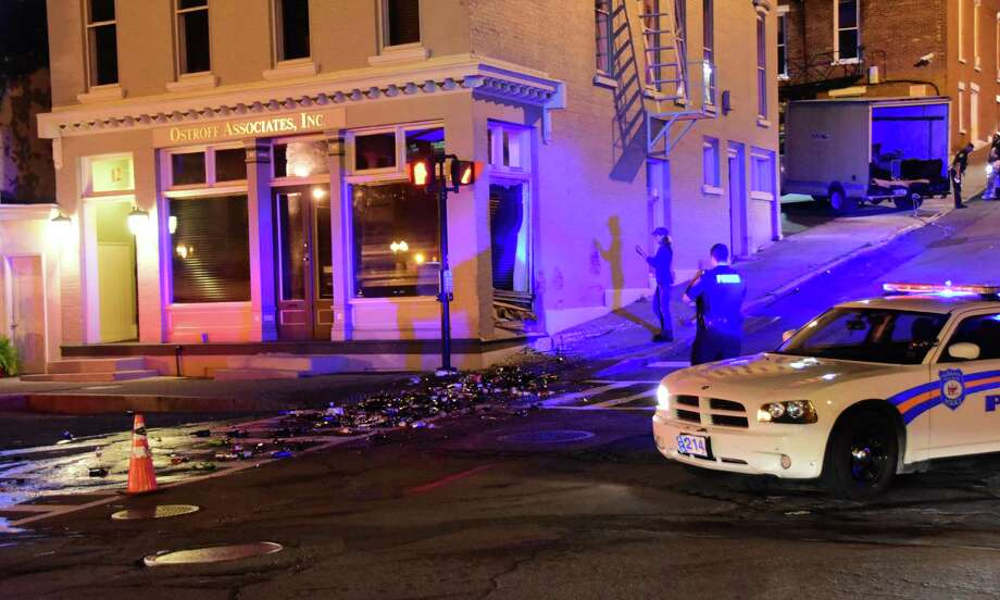 The box truck was backing out of a parking lot, top right, when the driver apparently lost control and rolled backward down the Chapel Street hill into the Ostroff Associates building in downtown Albany on Sept. 28, 2015. Beer and other bottles of alcohol spilled from the back of the truck and broke on the Sheridan Avenue sidewalk and street. (Steve Barnes/Times Union)