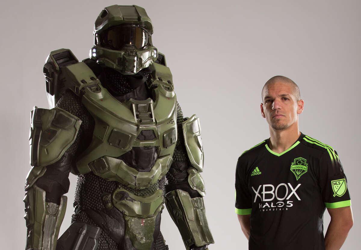 Sounders FC midfielder Osvaldo Alonso models the team's new 'Halo'-themed kit alongside game character Master Chief.