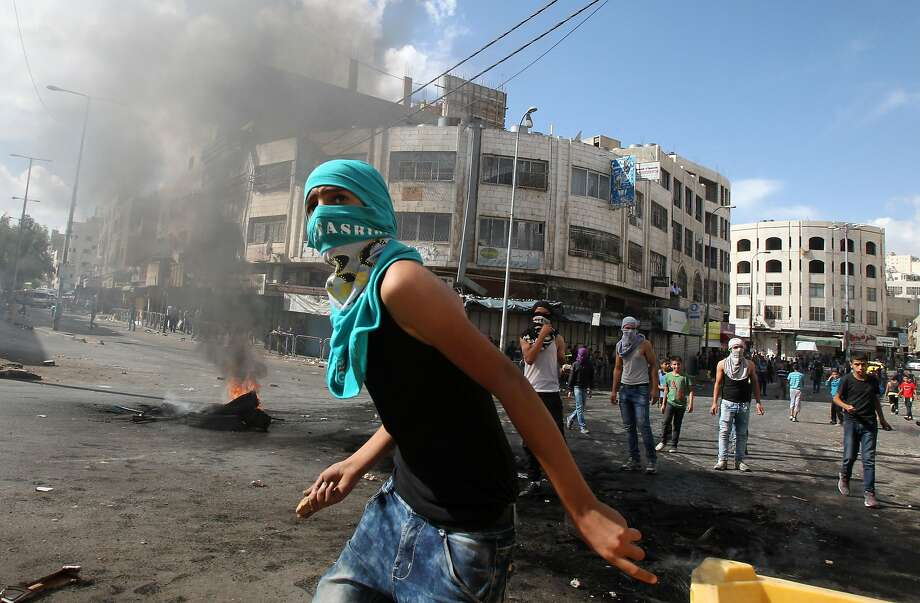 Palestinian protesters throw stones towards Israeli security forces in the West Bank town of Hebron during a demonstration in solidarity with fellow protesters at Jerusalem's flashpoint Al-Aqsa mosque. Photo: Hazem Bader, AFP / Getty Images