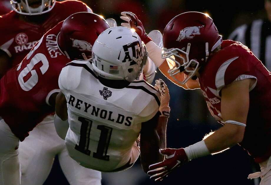 ARLINGTON, TX - SEPTEMBER 26:  Josh Reynolds #11 of the Texas A&M Aggies is tackled by Rohan Gaines #26 of the Arkansas Razorbacks and Brooks Ellis #51 in the first half during the Southwest Classic at AT&T Stadium on September 26, 2015 in Arlington, Texas.  (Photo by Ronald Martinez/Getty Images) Photo: Getty Images