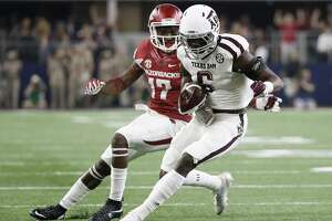 Texas A&M defensive back Donovan Wilson (6) comes away with an interception on a pass intended for Arkansas wide receiver JoJo Robinson (17) during the first half of an NCAA college football game Saturday, Sept. 26, 2015, in Arlington, Texas. (AP Photo/Tony Gutierrez)