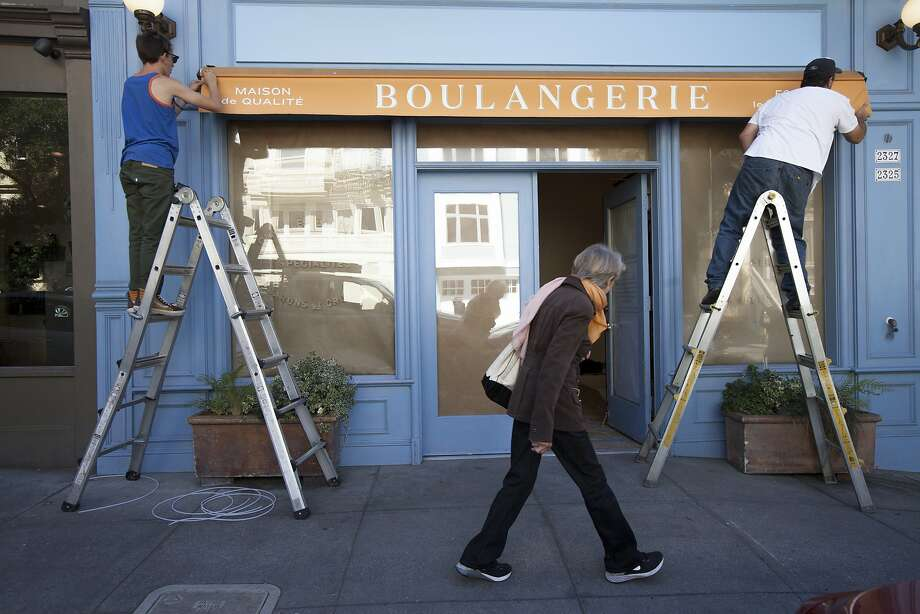 Walter LeMaster, CEO of Artisan Awning Company, right, sets up the new awning with his 17-year-old son Aaron Freese as a woman takes a peek inside La Boulangerie de San Francisco, Tuesday, Sept. 29, 2015, in San Francisco, Calif. Several shuttered La Boulange shops will reopen as La Boulangerie. The original Pacific Heights location at 2325 Pine St. will be the first to reopen. Photo: Santiago Mejia, Special To The Chronicle