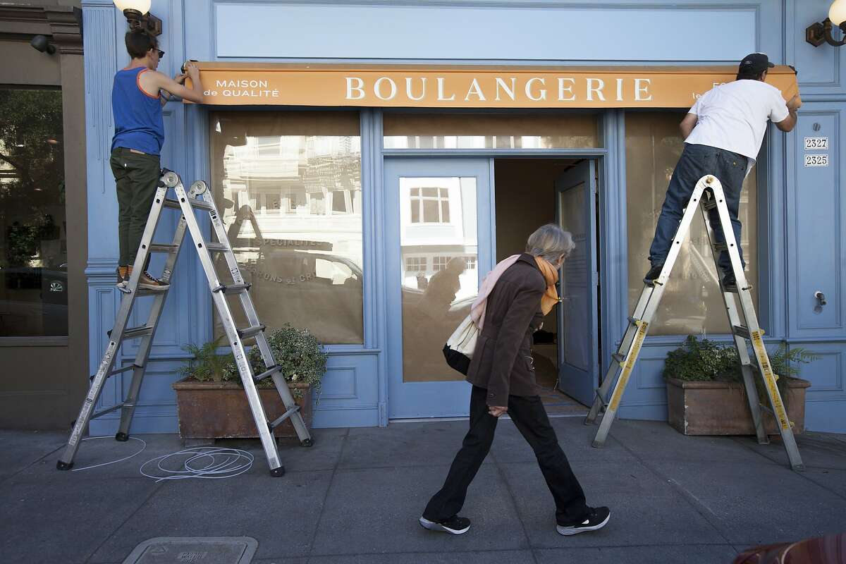 Walter LeMaster, CEO of Artisan Awning Company, right, sets up the new awning with his 17-year-old son Aaron Freese as a woman takes a peek inside La Boulangerie de San Francisco, Tuesday, Sept. 29, 2015, in San Francisco, Calif. Several shuttered La Boulange shops will reopen as La Boulangerie. The original Pacific Heights location at 2325 Pine St. will be the first to reopen.