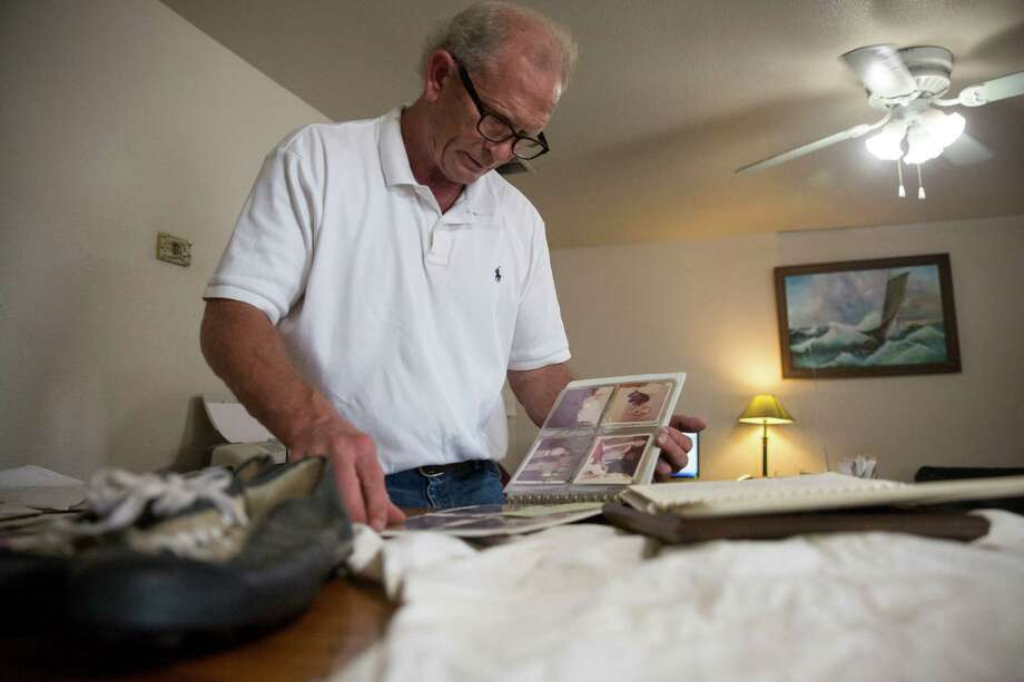 Richard Osborne looks through a family photo album at his office in San Antonio, Texas on September 23, 2015.  Forty years ago, his brother Bruce Osborne, who was then a promising high school football player, died. Photo: Carolyn Van Houten, Staff / San Antonio Express-News / 2015 San Antonio Express-News
