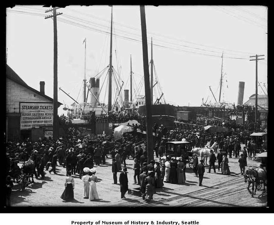"""By 1906, the Nome gold rush still had a major impact on Seattle. Fortune-hunters crowded Seattle looking for a ship to take them north. Businesses boomed as people bought supplies for the gold camps. In the three days before this photo was taken, more than 2,000 passengers and 12,000 tons of freight sailed north on five steamers.In this photo, crowds fill the Seattle waterfront to watch ships loaded with passengers and freight leave for Alaska."" -MOHAI Photo: Courtesy Museum Of History And Industry,  Image Number 1983.10.7520"