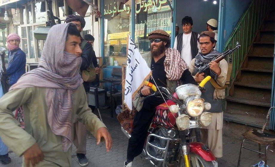 A Taliban fighter, center, was among many fanning out Tuesday in Kunduz, Afghanistan. The city was captured in a major setback to the government. Photo: Uncredited, STR / AP