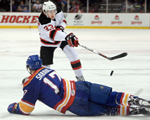 Albany Devils's #33 Corbin McPherson, top, blasts the puck over Norfolk Admirals #17 Charles Sarault during Saturday's game at the Times Union Center  March 21, 2015 in Albany, NY.  (John Carl D'Annibale / Times Union) ORG XMIT: MER2015092917005872 Photo: John Carl D'Annibale / 00030124O