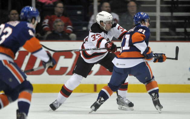 Corbin McPherson, center, with the Albany Devils defends against Kael Mouillierat during their game against the Bridgeport Sound Tigers at the Times Union Center on Sunday, Nov. 23, 2014, in Albany, N.Y.  (Paul Buckowski / Times Union) ORG XMIT: MER2015092917012173 Photo: Paul Buckowski / 00029286C