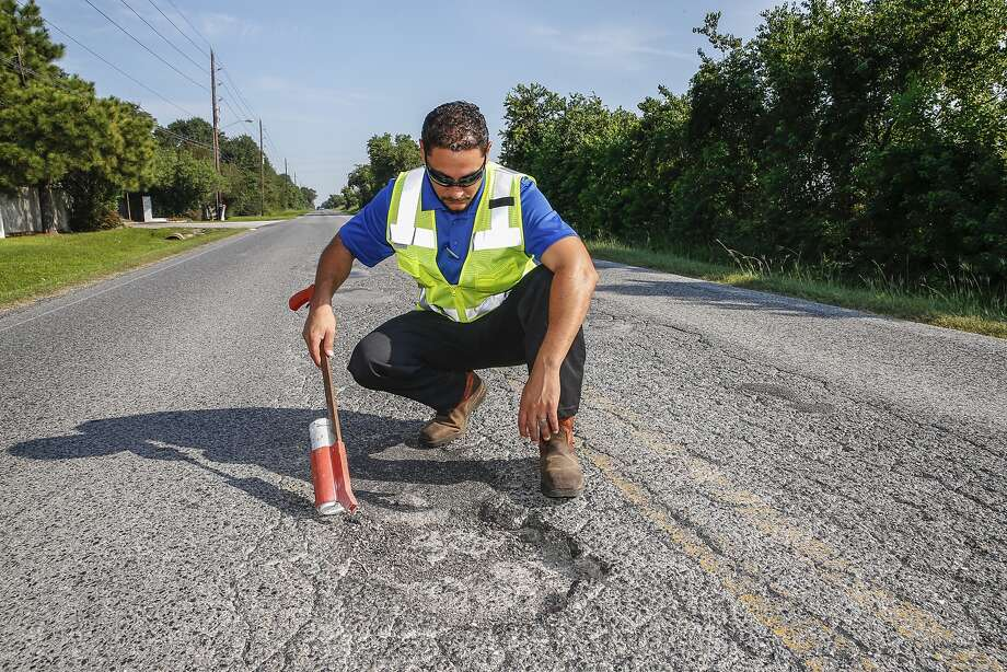 Jason Rivera, Katy assistant director of public works,  surveys potholes and disintegrating asphalt on Katy Hockley Cutoff Road in front  of the Heritage West subdivision in north Katy. In its new budget, Katy will focus on street projects. Photo: Diana L. Porter, Freelance / © Diana L. Porter