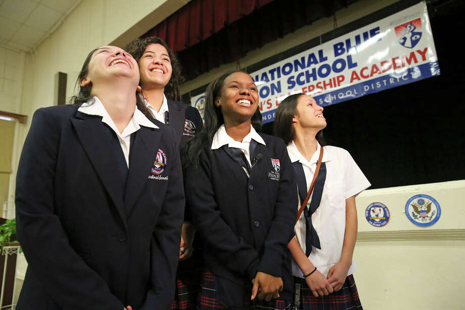 Students Azeal Garza (from left) Meg Garcia Karease Williams and Mallory Sanchez enjoy the glory as Principal Delia McLerran announces to the student body assembled on September 29, 2015 at the SAISD's Young Women's Leadership Academy,  that the school has been recognized  as a 2015 National Blue Ribbon School  on September 29, 2015. Photo: Tom Reel / San Antonio Express-News