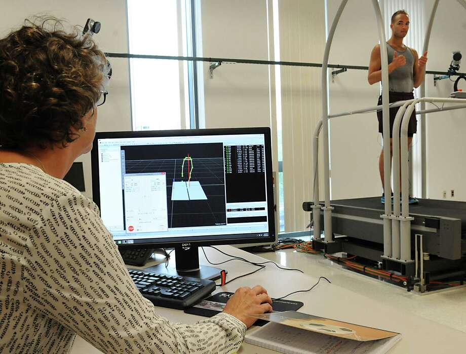 Research Scientist Lynn McCane, left, sits at a computer to monitor volunteer Devon Barlow on motion capture treadmill during an open house at newly designated NIH National Center for Adaptive Neurotechnologies at David Axelrod Institute on Tuesday, Sept. 29, 2015 in Albany, N.Y. The treadmill is a gait analysis system that measures a person's gait before and after physical therapy. The room has multiple cameras mounted on wall. (Lori Van Buren / Times Union) Photo: Lori Van Buren / 00033517A