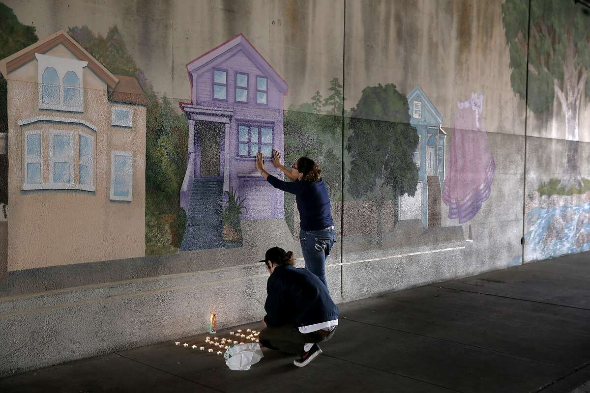 The sister of the victim touches the mural her brother worked on at the 3500 block of West St. in Oakland, Calif. where Antonio Ramos was shot and killed on Tues. September 29, 2015, as a friend lights candles. The purple Victorian is the artists' home.