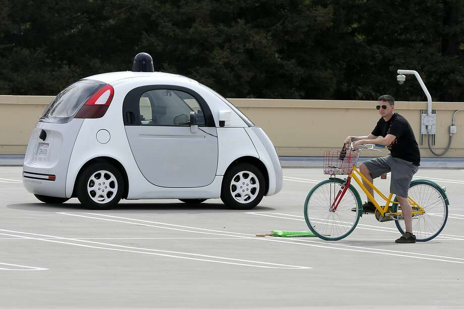 A prototype self-driving vehicle Google built drives past an obstacle Ñ the man on the bicycle Ñ during a test drive on the roof of a Google building in Mountain View, California, on Tuesday, Sept. 29, 2015. Photo: Connor Radnovich, The Chronicle