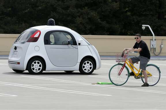 A prototype self-driving vehicle Google built drives past an obstacle Ñ the man on the bicycle Ñ during a test drive on the roof of a Google building in Mountain View, California, on Tuesday, Sept. 29, 2015.