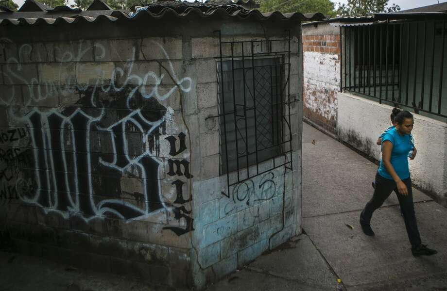A woman passes a wall with MS-13 graffiti at Villa Mariona II in San Salvador, El Salvador on March 7, 2014. Photo: AFP, AFP/Getty Images