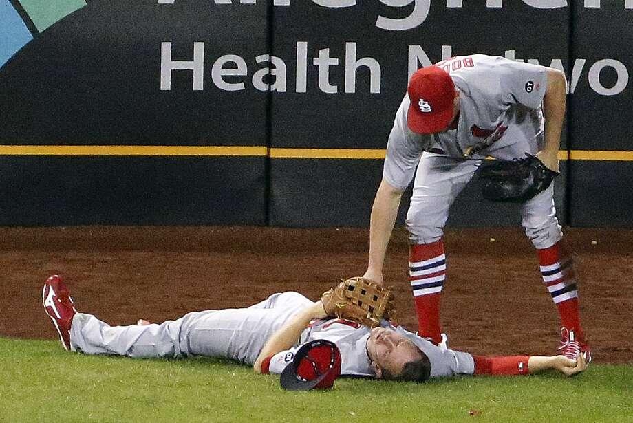 St. Louis' Peter Bourjos checks on teammate Stephen Piscotty after they collided. Photo: Gene J. Puskar, Associated Press