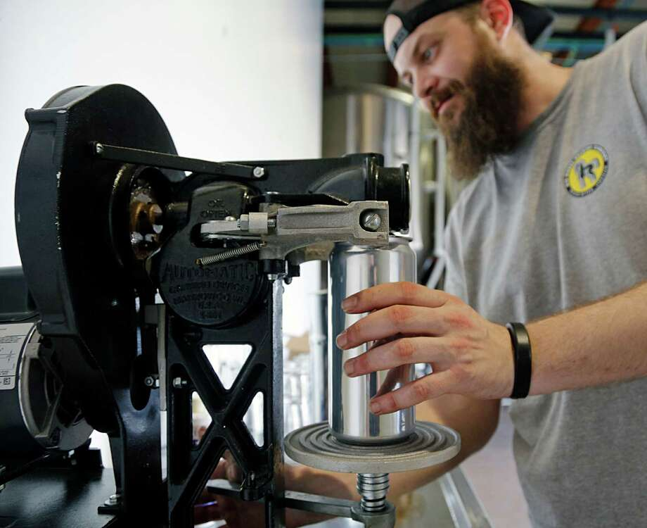 Robbie Cummings with Brash Brewing demonstrates a crowlers machine Tuesday, Sept. 29, 2015, in Houston.