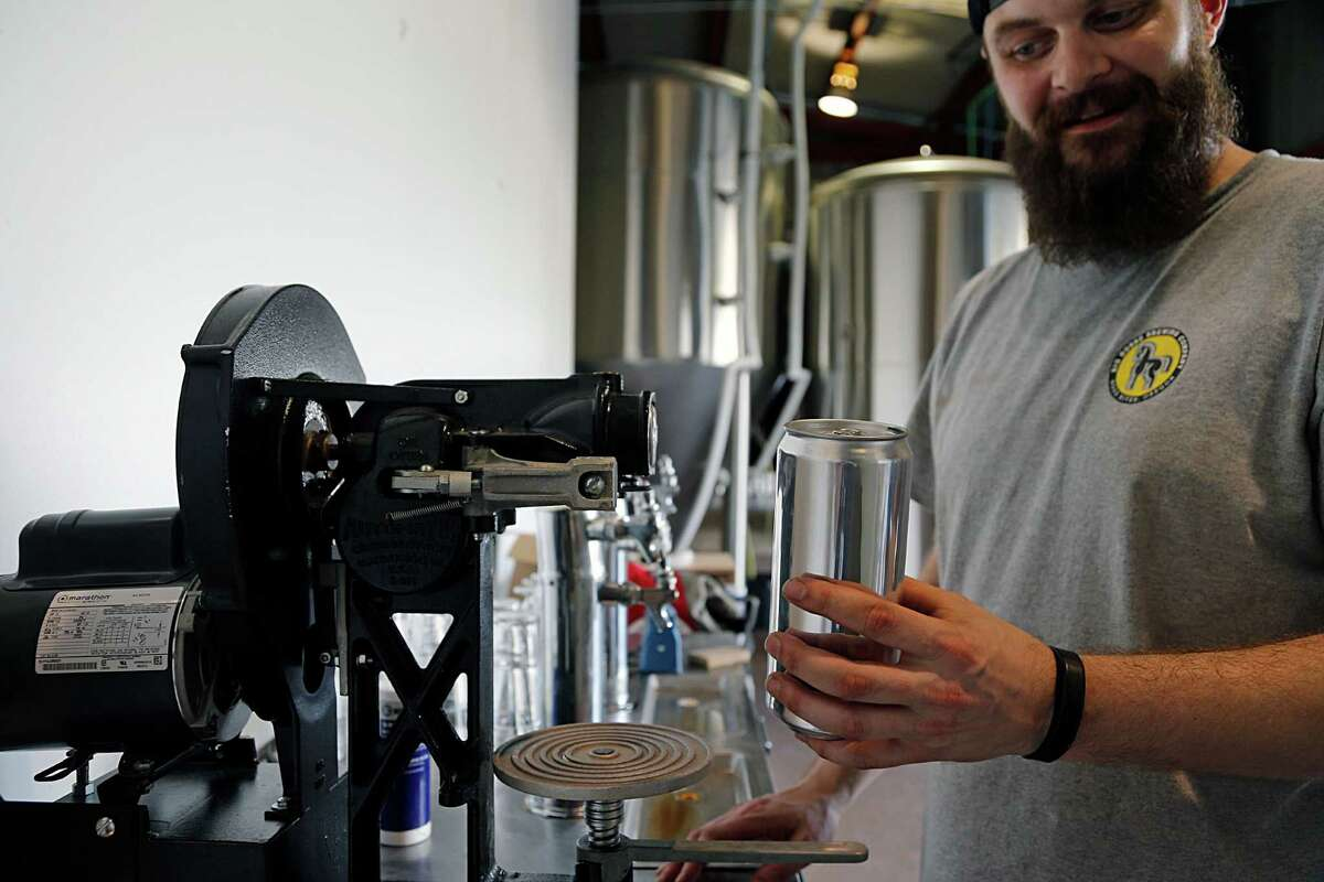 Robbie Cummings with Brash Brewing demonstrates a crowlers machine Tuesday, Sept. 29, 2015, in Houston. ( James Nielsen / Houston Chronicle )