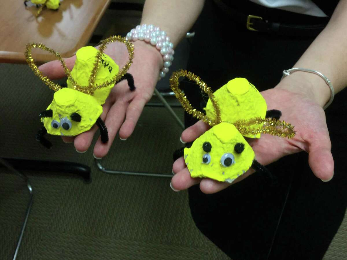 """Alina Boie, a psychologist in the school district, shows the """"bees"""" made of egg cartons and pipe cleaners that Glenville School students will hand out Wednesday at the Starbucks on Greenwich Avenue to promote the district's Log Off and Listen In Day."""