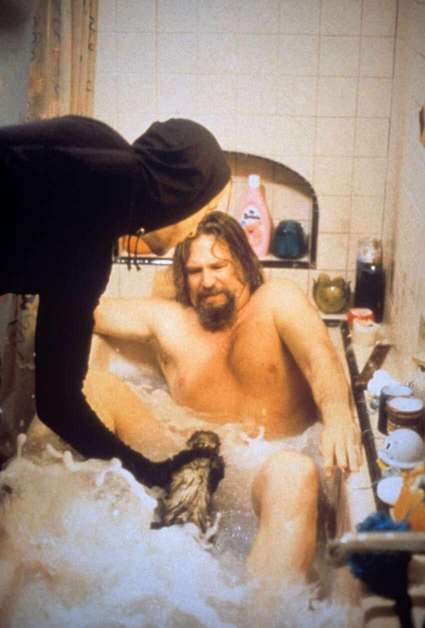 A scene from the movie The big Lebowski, where the American actor Jeff Bridges plays the role of Dude, a breezy loafer, who is subjected to threats while having a bath at home by a man wearing a black disguise who keeps a ferret. USA, 1998.. (Photo by Mondadori Portfolio via Getty Images)