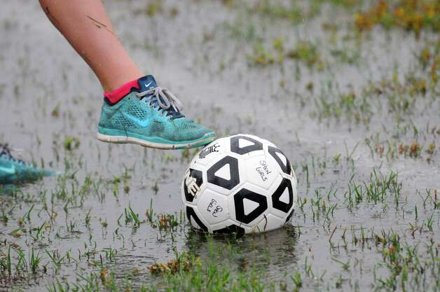 Ball girl 12-year-old Rylee Gwiazdowski retrieves a ball from a sideline puddle as Colonie and Shenendehowa battle it out in a steady rain during their girl's high school soccer game on Tuesday Sept. 29, 2015 in Clifton Park  , N.Y.  (Michael P. Farrell/Times Union) Photo: Michael P. Farrell / 00033521A