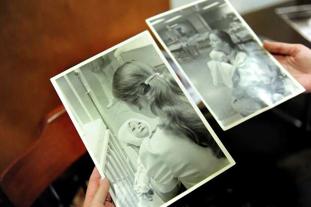 Amanda Scarpinati looks at photographs of herself on Tuesday, Sept. 29, 2015, at Albany Medical Center in Albany, N.Y. Scarpinati, the infant in the picture, was reunited with Sue Berger, the nurse she was seeking via social media. (Cindy Schultz / Times Union) Photo: Cindy Schultz / 00033514A