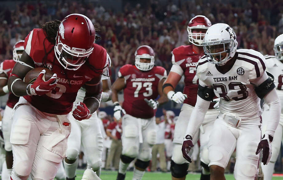 Arkansas' Alex Collins, left, runs for a 4-yard touchdown as part of his 151-yard game against the Texas A&M defense on Saturday night at Arlington. Photo: Ronald Martinez, Staff / 2015 Getty Images