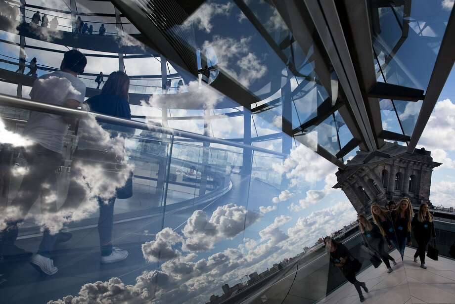 Clouds are reflected in the cupola of the Reichstag building that houses the lower house of parliament in Berlin, on September 29, 2015. The cupola was designed by British architect Norman Foster. Photo: Kay Nietfeld, AFP / Getty Images