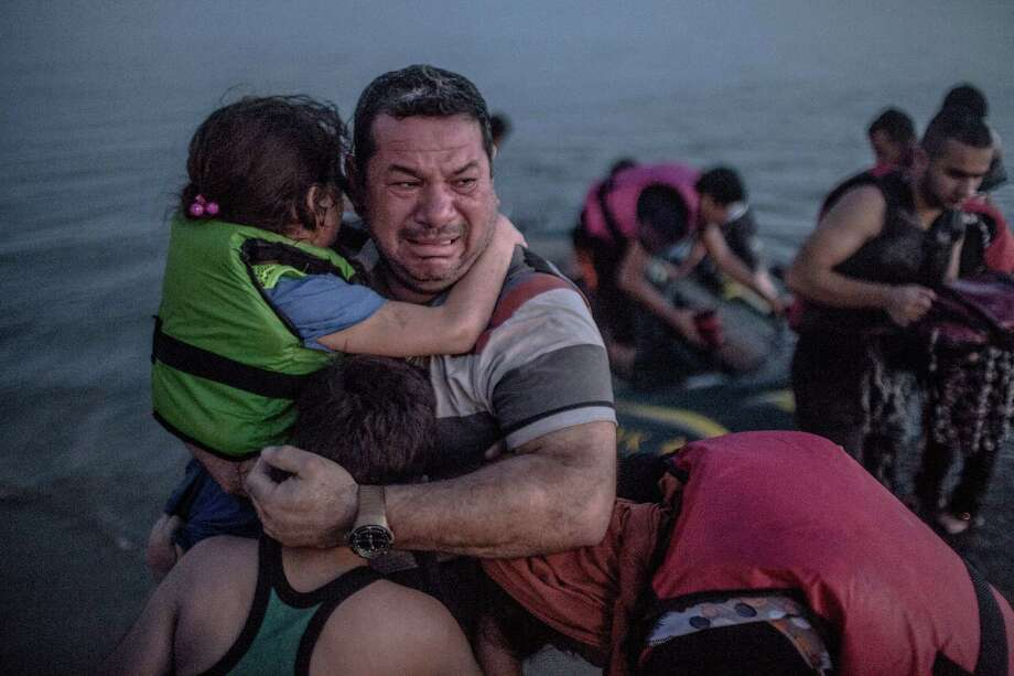 Iraqi refugee Laith Majid held his daughter and son and cried joyously after they arrived in Kos Greece, on Aug. 15 on a crowded, flimsy, inflatable rubber boat. Photo: Daniel Etter /New York Times / NYTNS