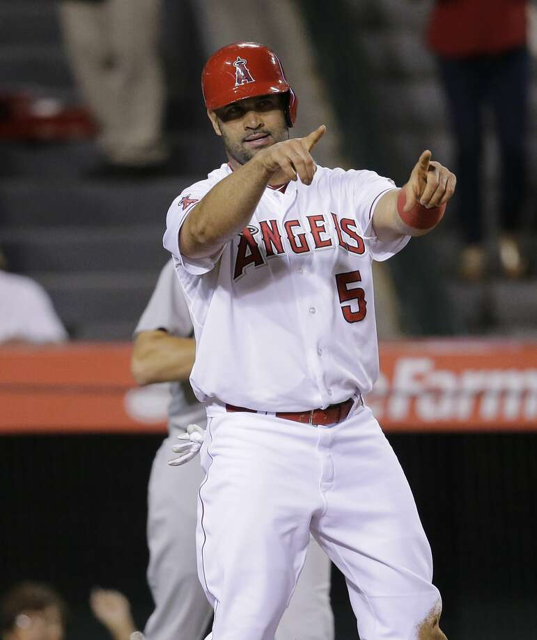 Los Angeles Angels' Albert Pujols points to teammate David Freese after he scored on a single hit by Freese during the fifth inning of a baseball game against the Oakland Athletics, Tuesday, Sept. 29, 2015, in Anaheim, Calif. (AP Photo/Jae C. Hong) Photo: Jae C. Hong, Associated Press