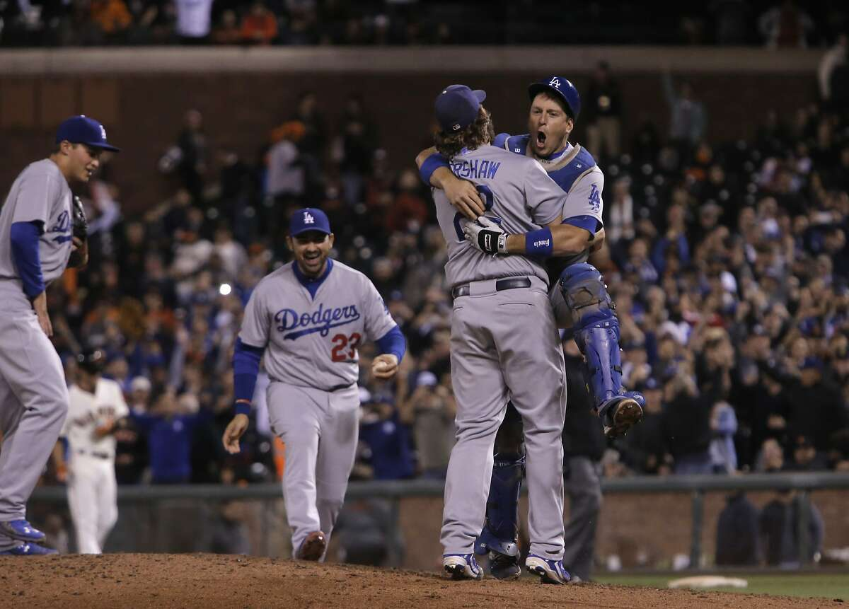 Pitcher Clayton Kershaw celebrates with catcher A. J. Ellis as the Los Angeles Dodgers beat the San Francisco Giants 8-0 at AT&T Park in San Francisco, Calif., on Tues. September 29, 2015.